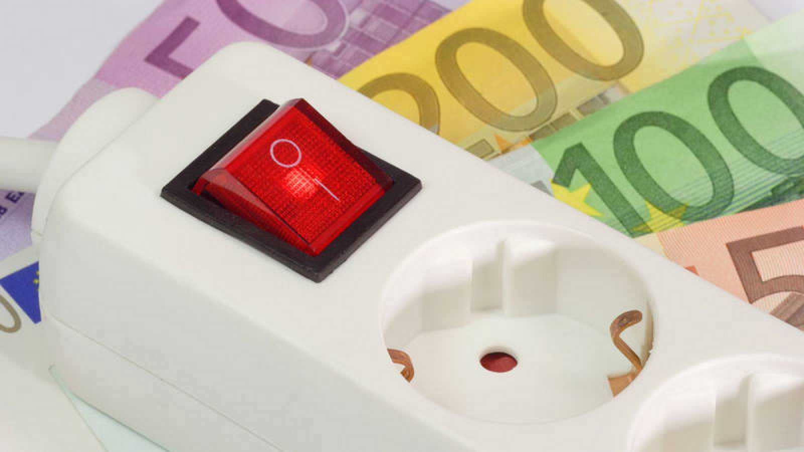 Una regleta de enchufes sobre varios billetes de euro