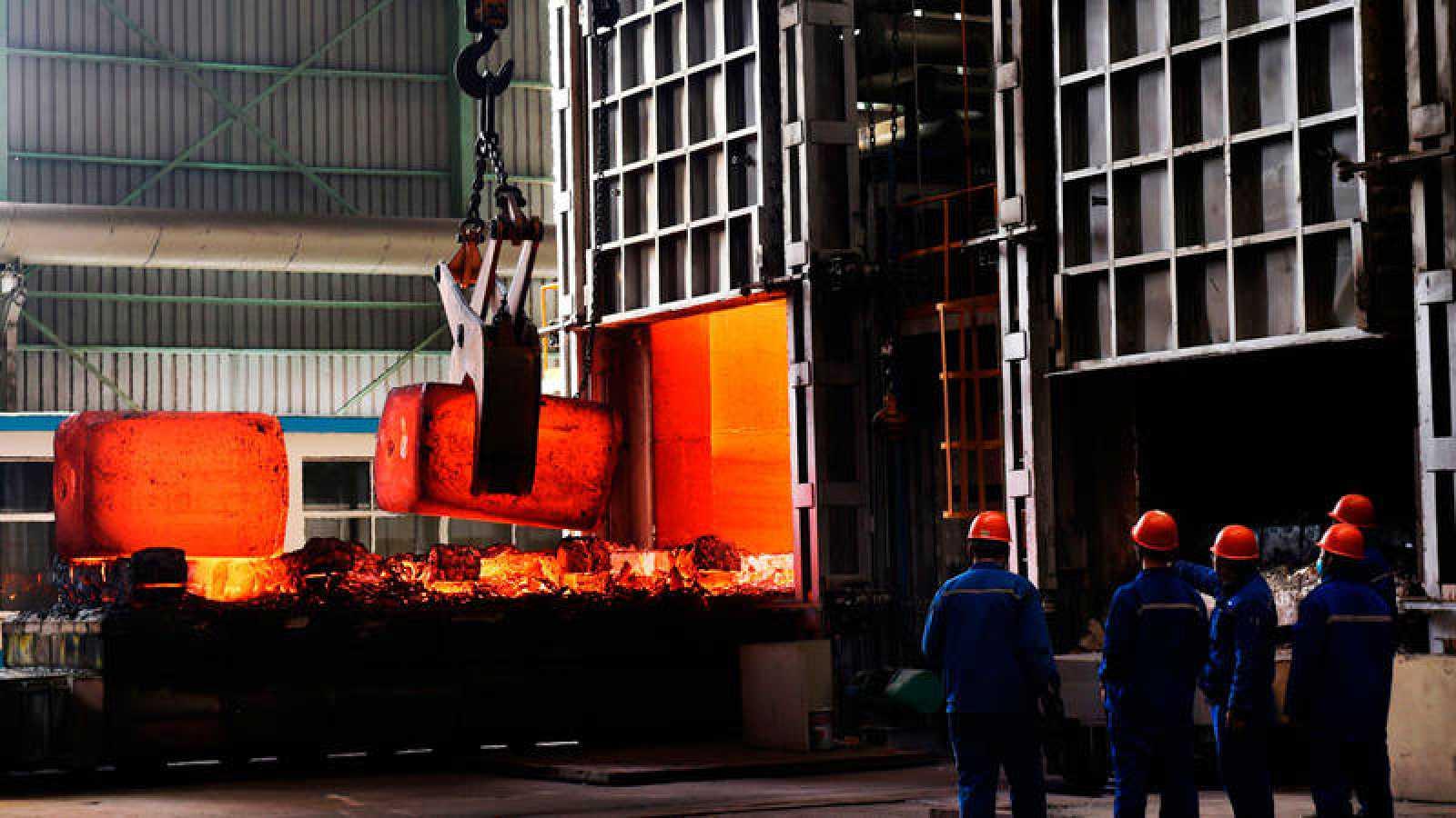 Empleados chinos observan varios bloques de acero candente en una planta de la provincia de Shandong