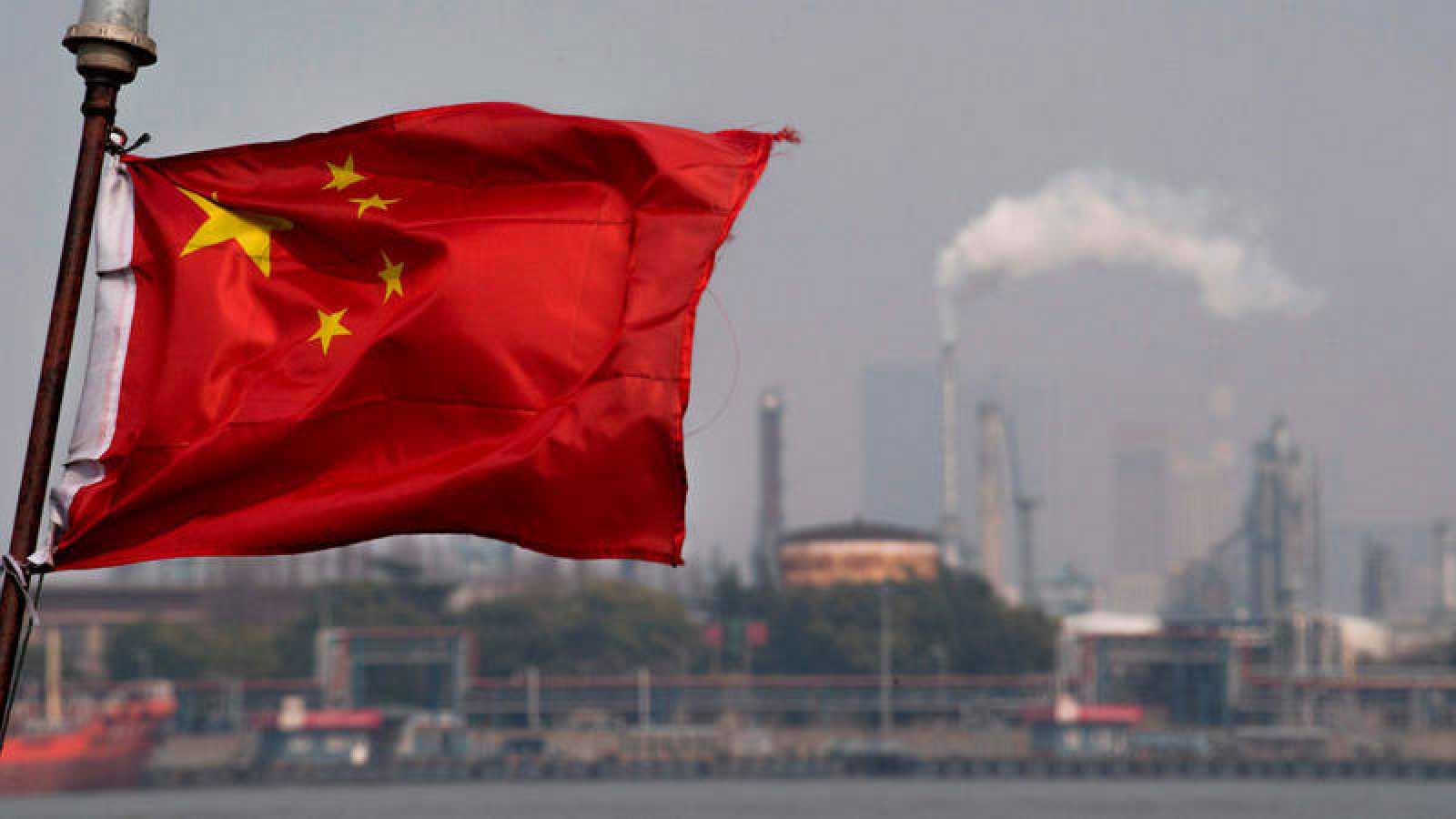 La bandera de China ondea en el puerto de Shanghai, frente a la refinería de la petrolera Gaoqiao