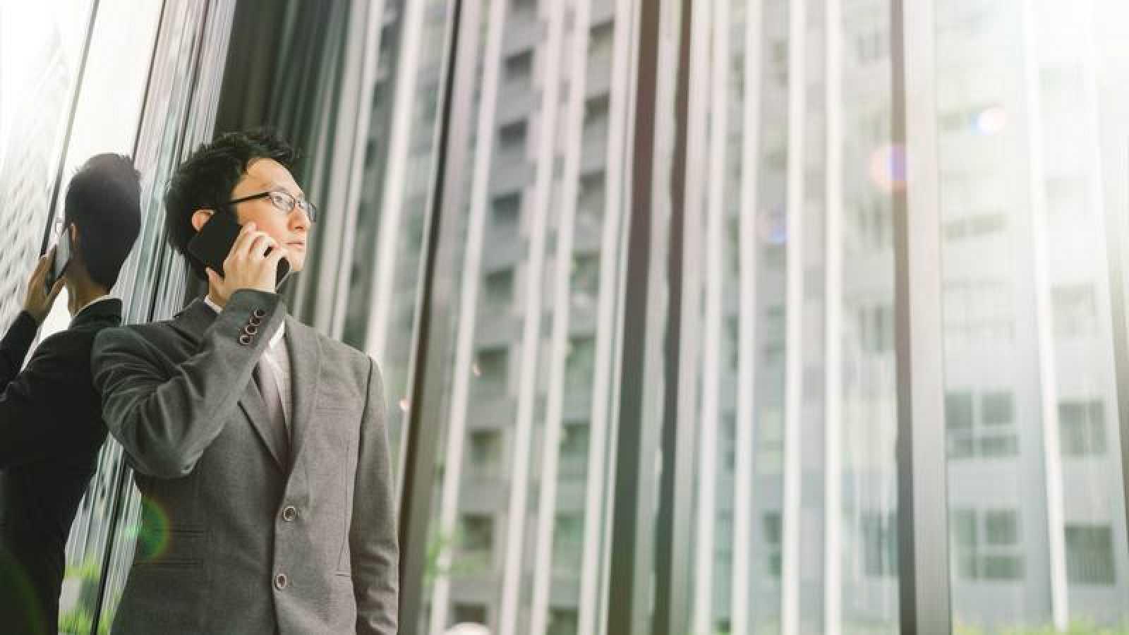 Un hombre de negocios asiático habla por el móvil desde un rascacielos