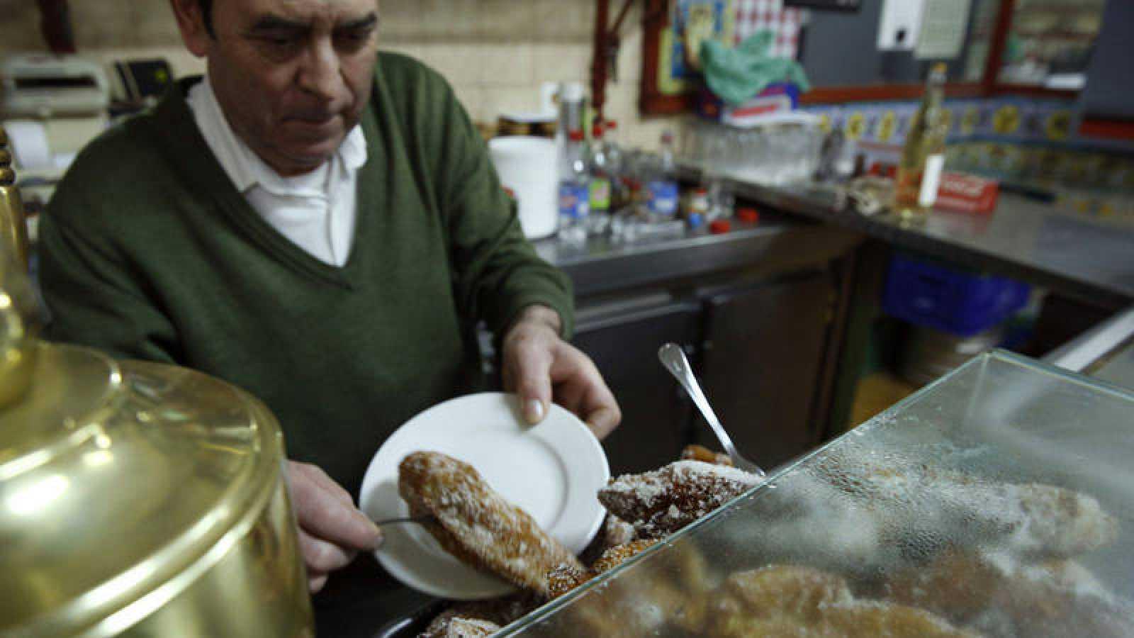 Un camarero sirve torrijas en un establecimiento del centro de Madrid