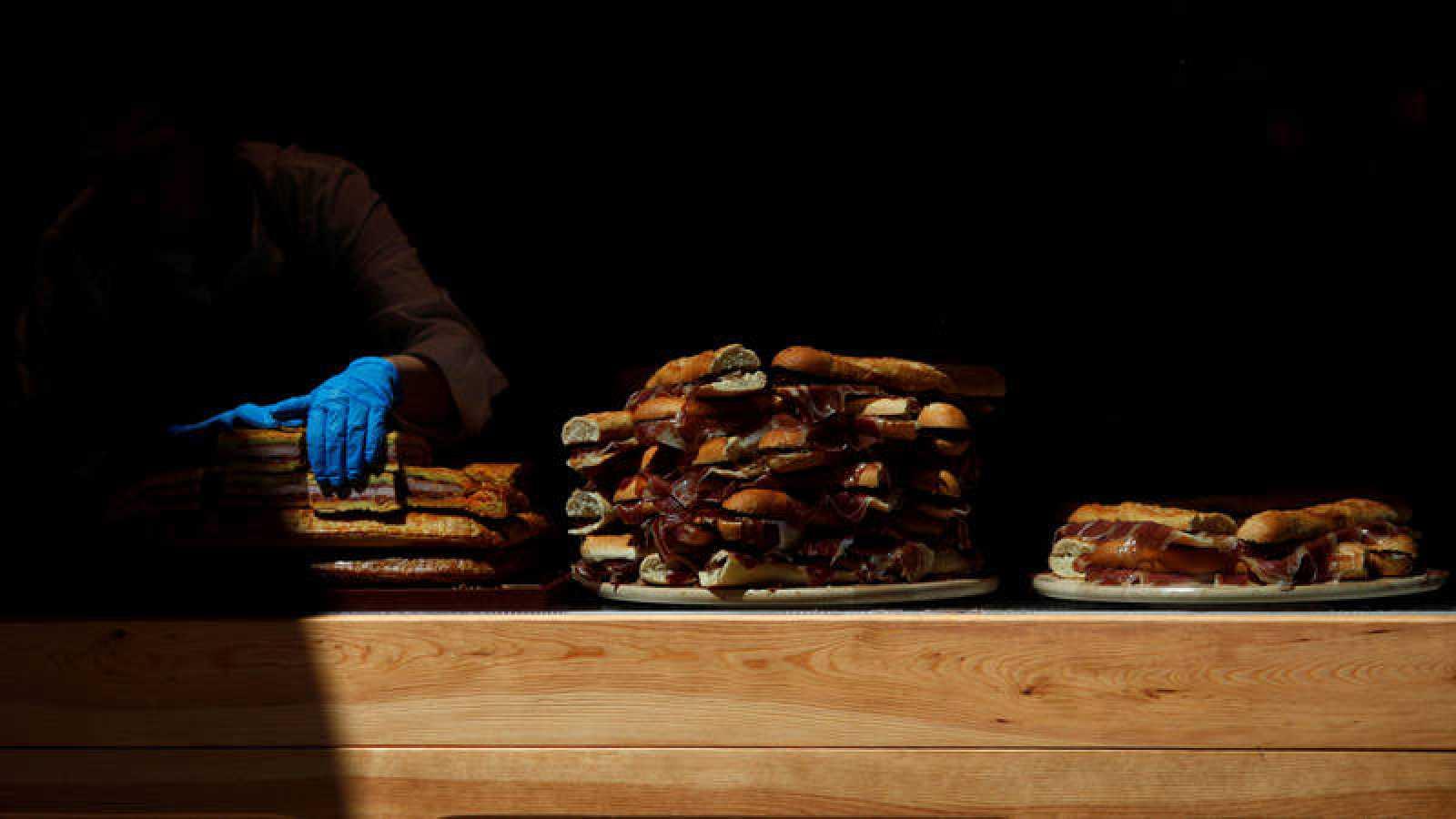 Una camarera coloca productos ibéricos en un mostrador