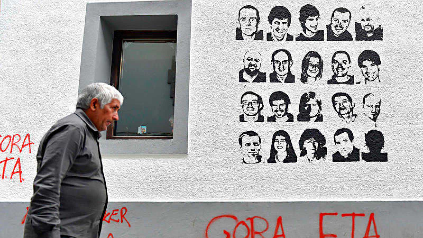 Un hombre pasa ante una pintada que reivindica a los presos de ETA en Hernani