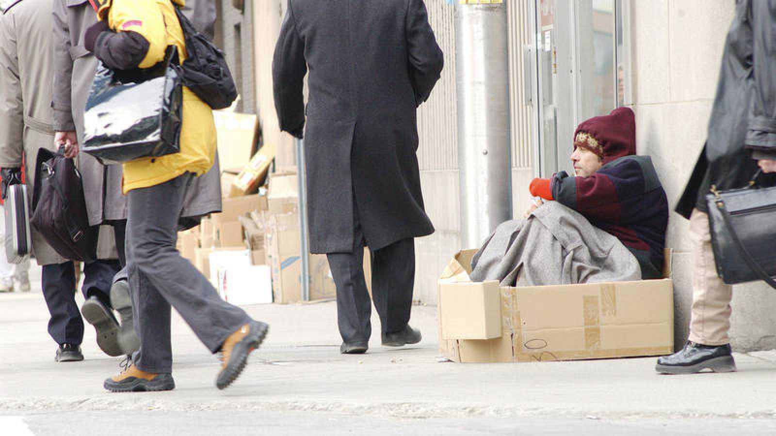 Varias personas pasan por delante de un mendigo