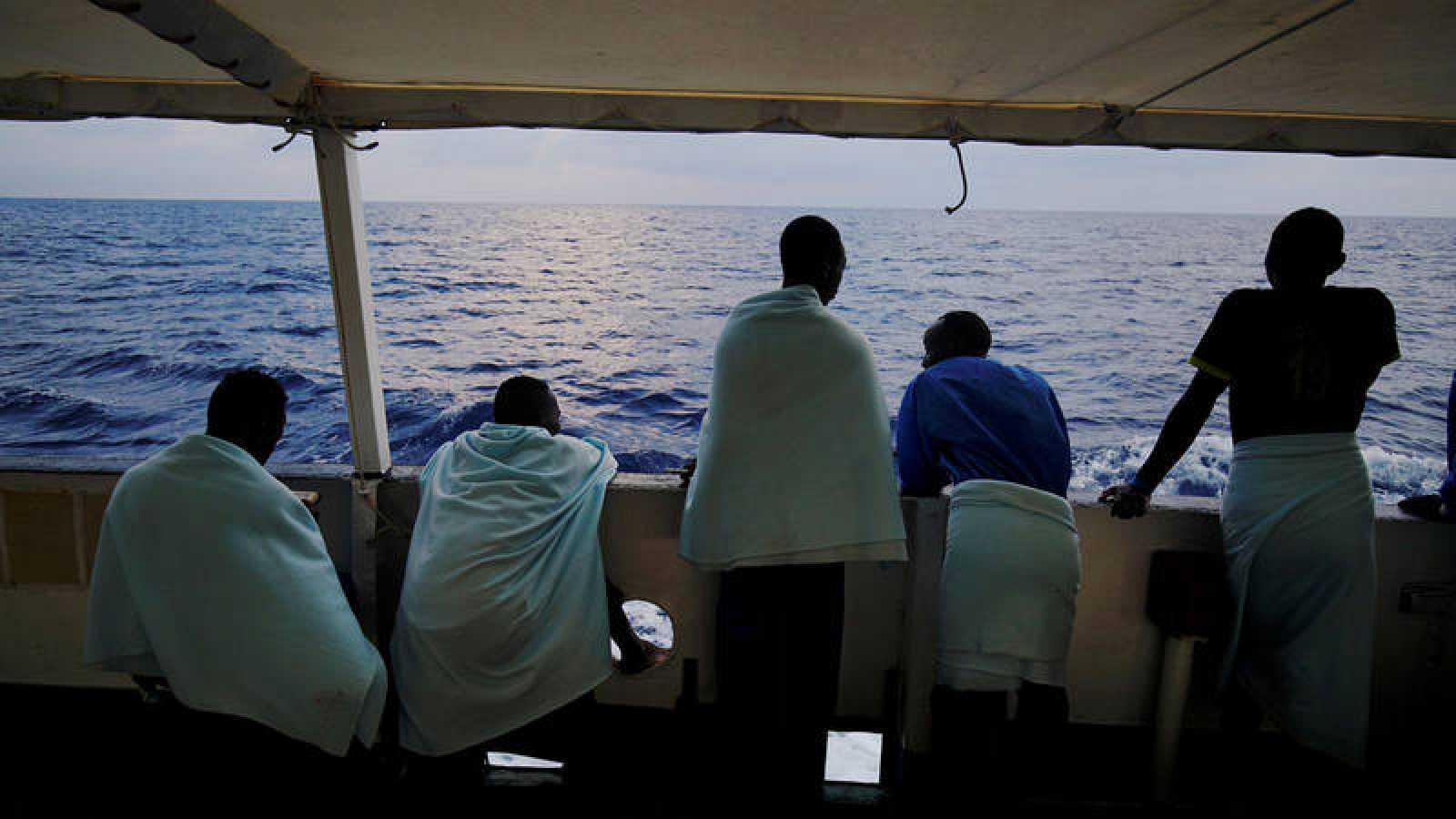 Cinco migrantes observan el Mediterráneo desde el barco de la ONG Proactiva Open Arms.