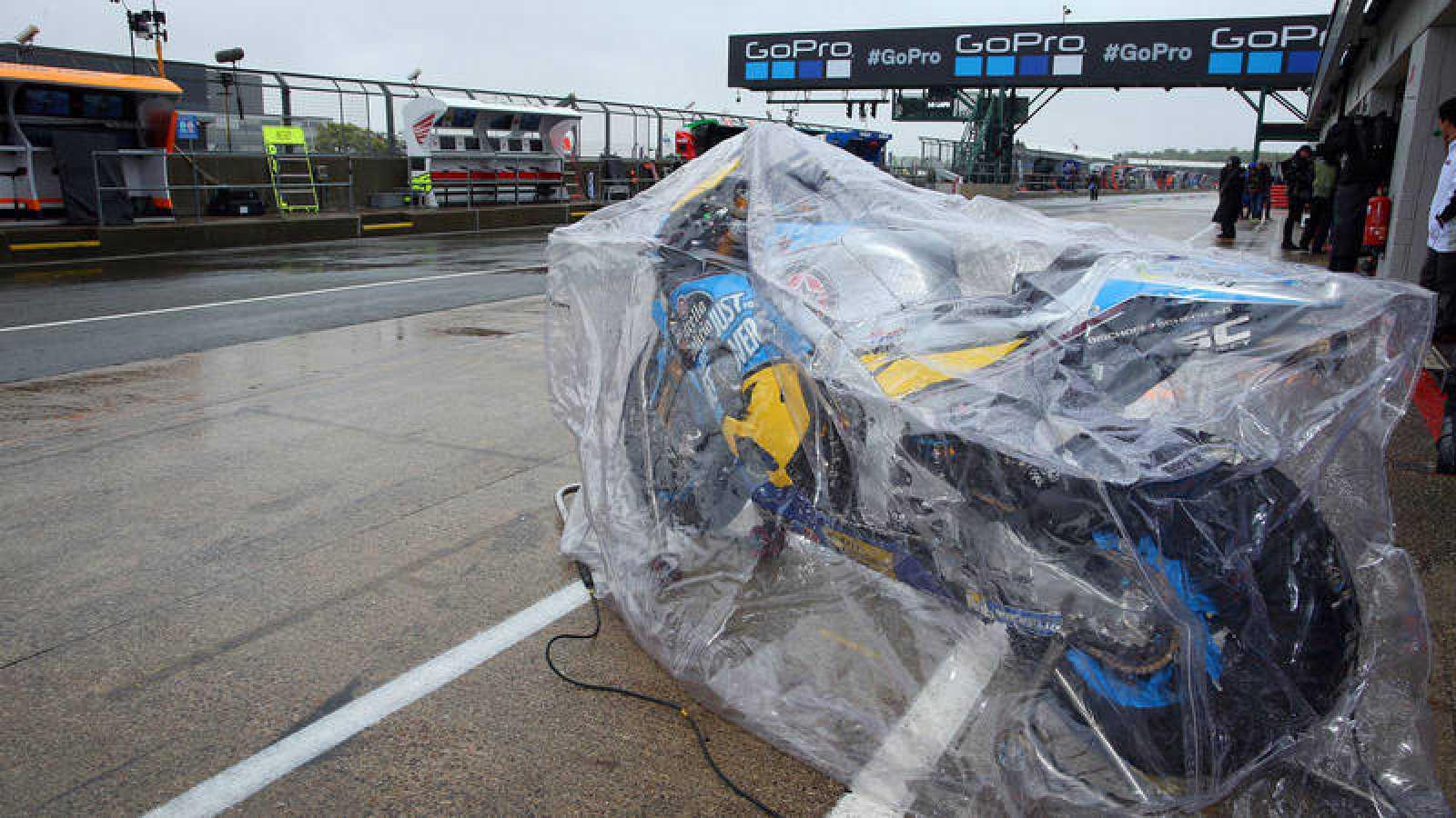 Una moto aguarda en el box de Silverstone, protegida por un plástico por la lluvia.