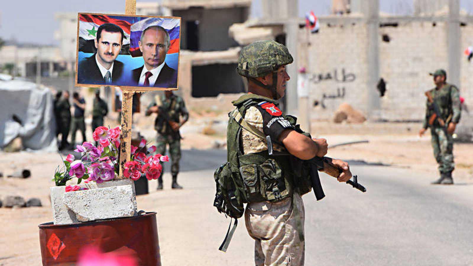 Soldados sirios custodian un paso cerca de Idleb, adornado con un retrato doble de Bachar al Asad y Vladímir Putin