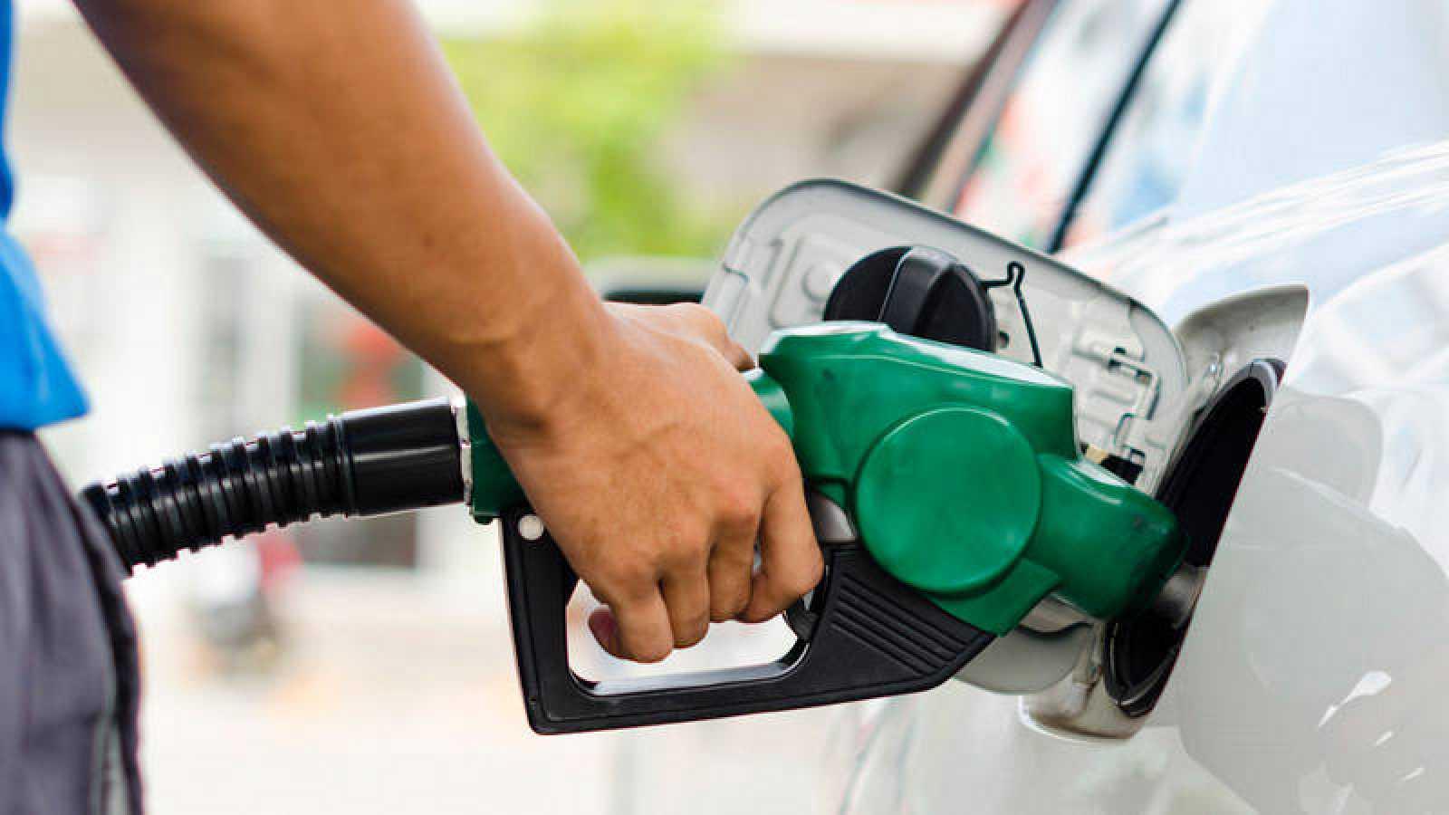 Un consumidor reposta combustible en una gasolinera