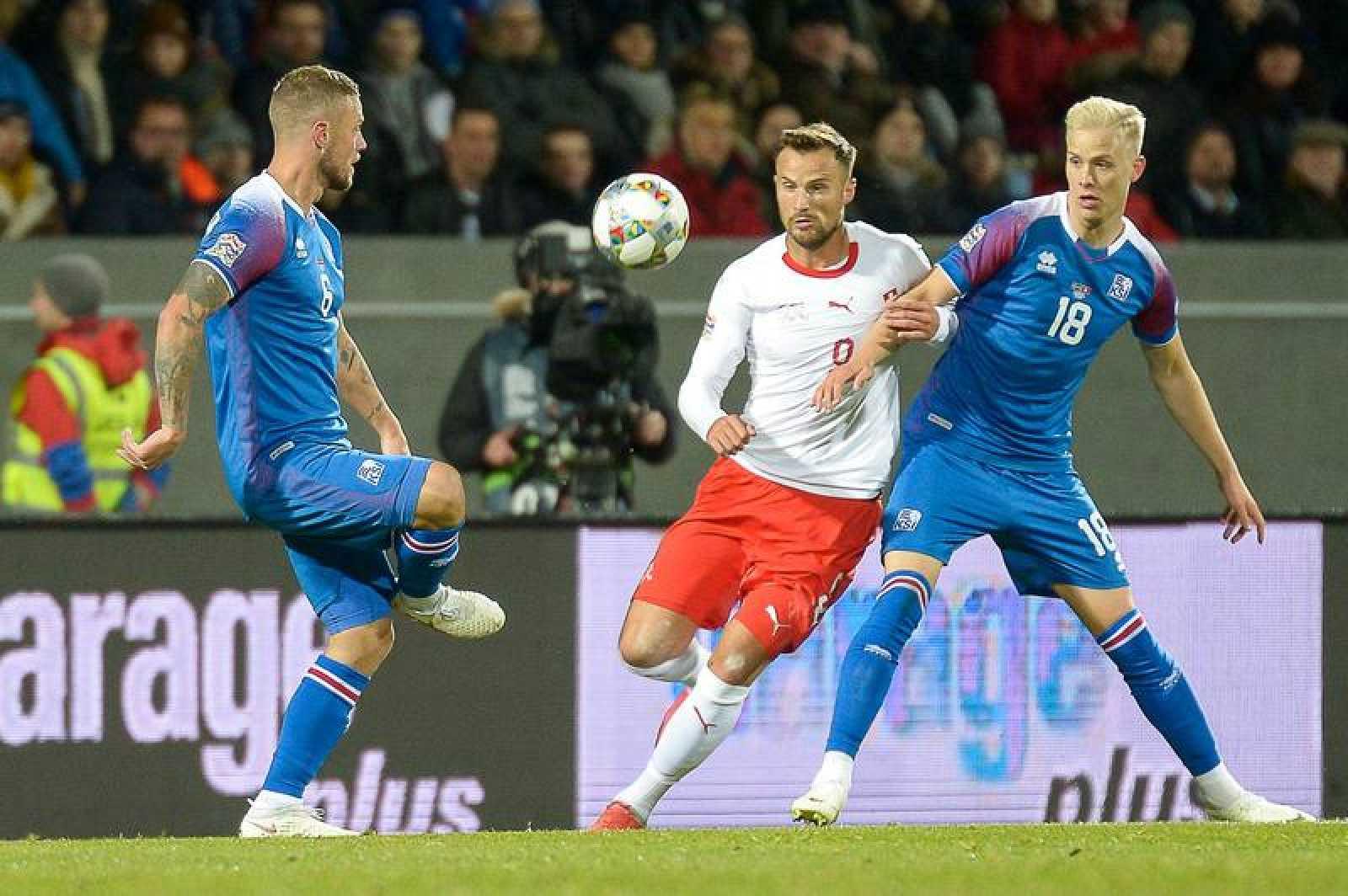 El suizo Freuler pelea por el balón con los islandeses Sigurdsson (i) y Magnusson (d)