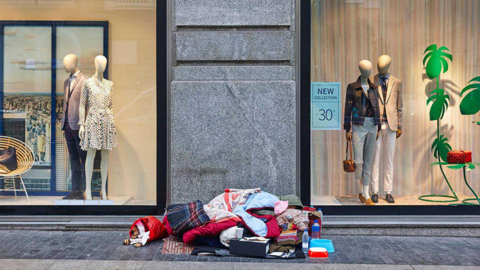 Una mujer duerme en la acera de una gran ciudad bajo los esaparates de una tienda de moda.