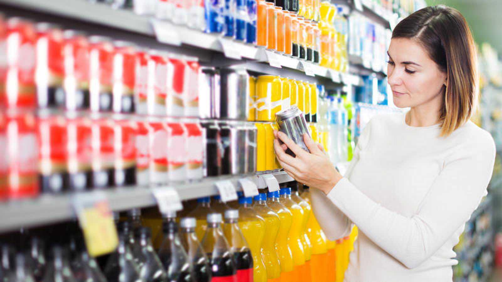 Una mujer mira la etiqueta de un refresco en un supermercado.