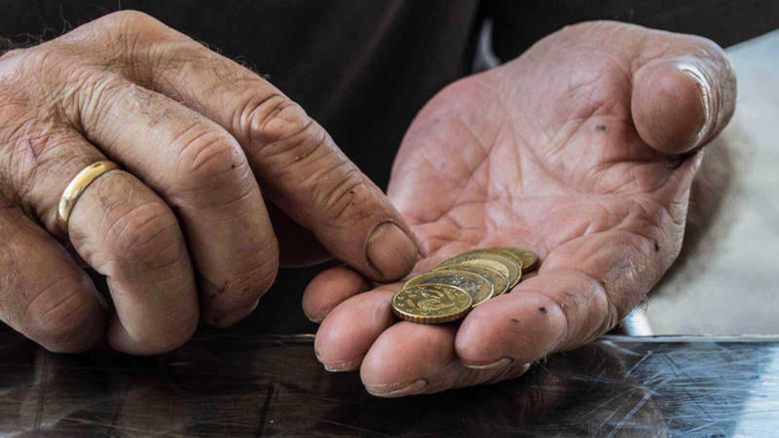 Una persona mayor cuenta monedas