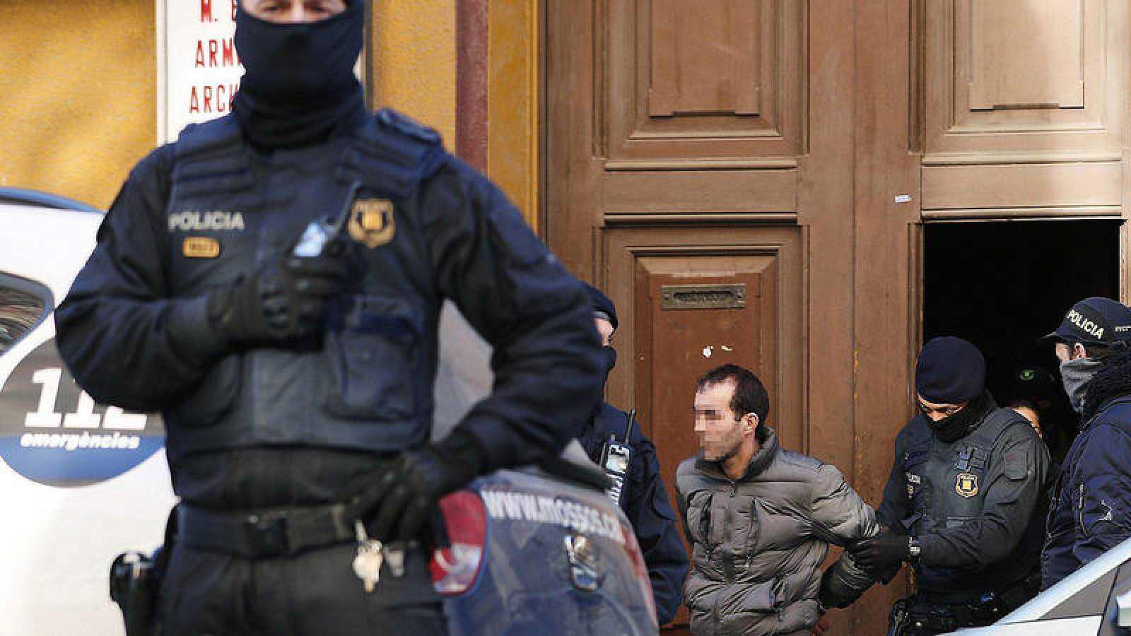 Los Mossos d,Esquadra trasladan a uno de los detenidos en el distrito de el Clot de Barcelona, tras efectuar desde primera hora de la mañana una operación antiterrorista contra una célula yihadista en Barcelona e Igualada. EFE/Alejandro García