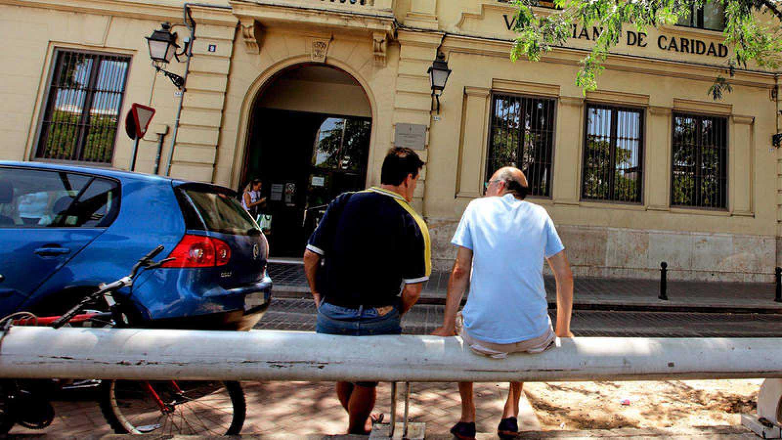 Imagen de archivo de dos hombres sentados ante la Casa de la Caridad de Valencia