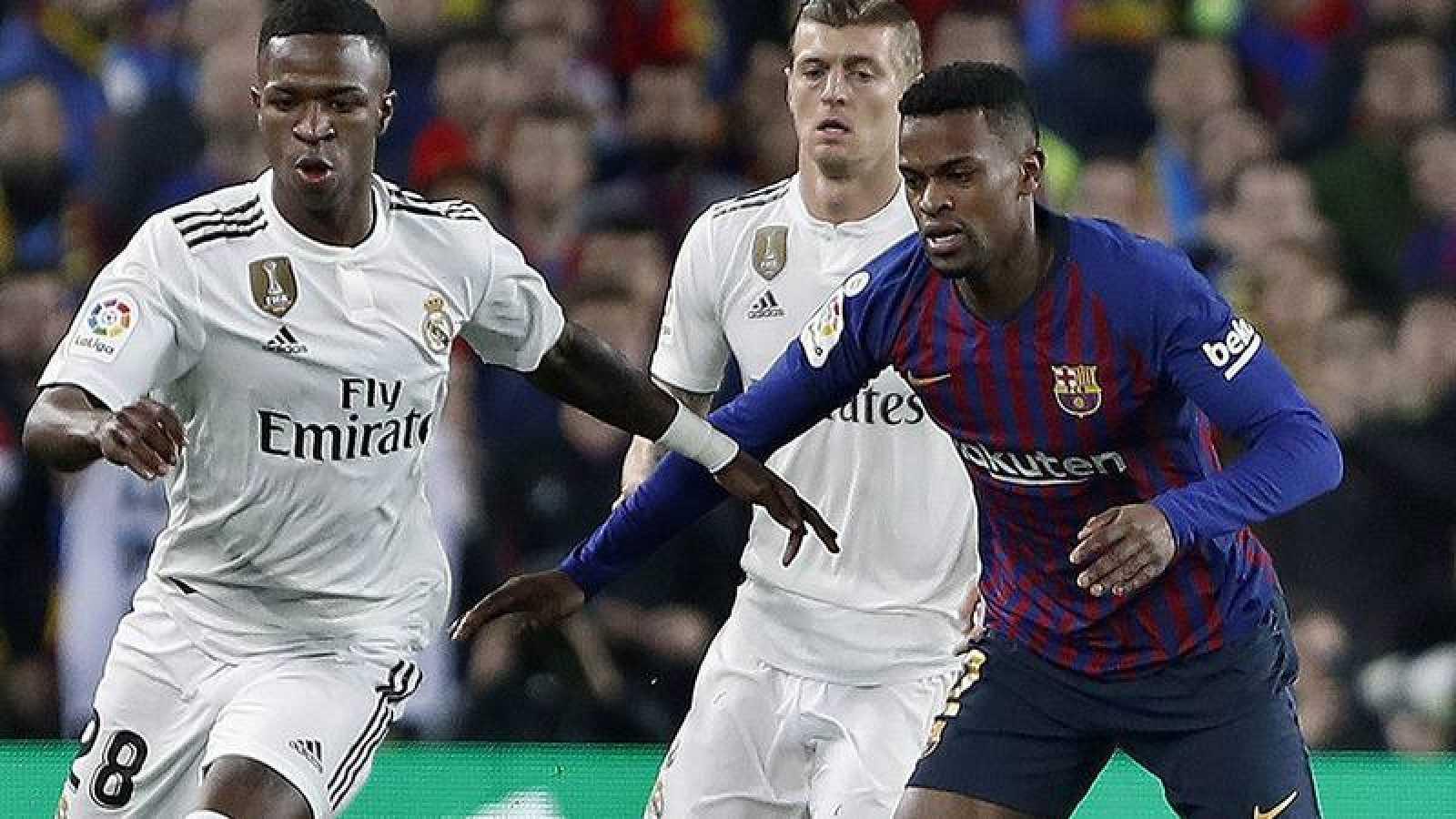 El delantero brasileño del Real Madrid, Vinicius Júnior (i), pelea un balón con el delantero brasileño del FC Barcelona, Malcom (d), en el partido de ida.