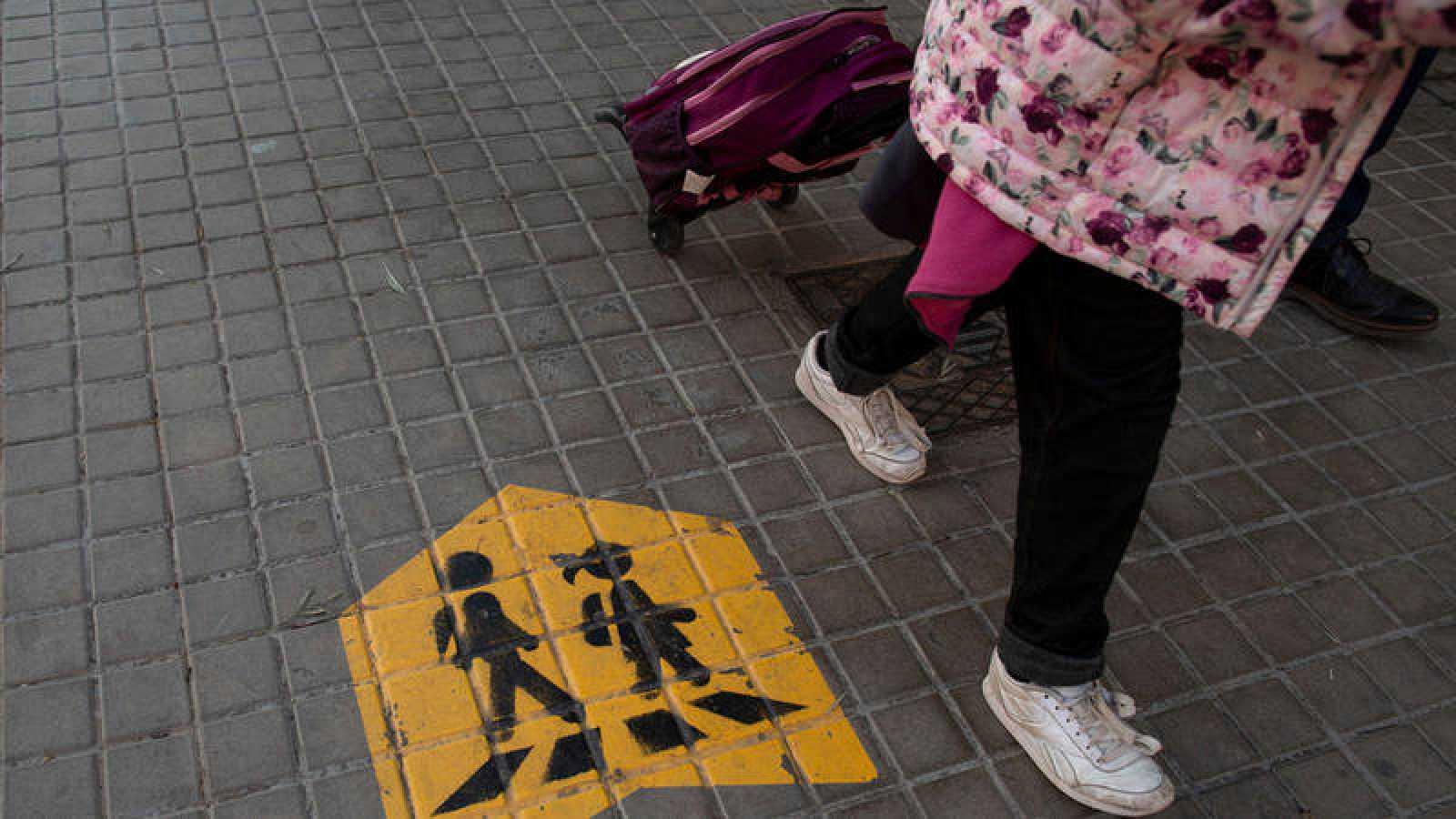 Niños caminando con mochila de ruedas.