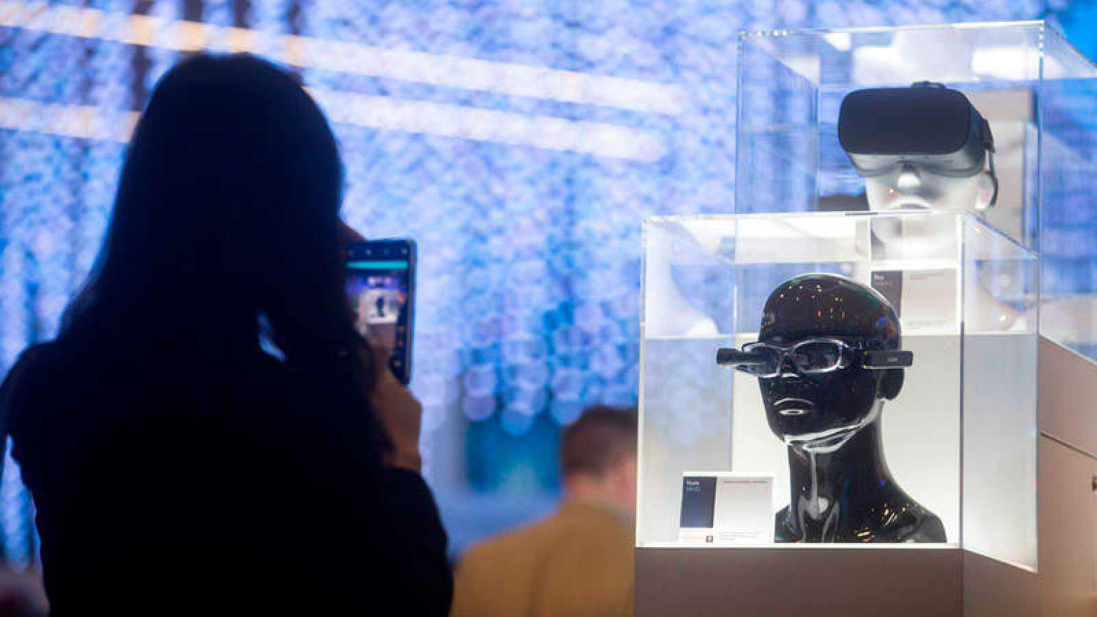 Una mujer fotografía un dispositivo tecnológico durante el Mobile World Congress.