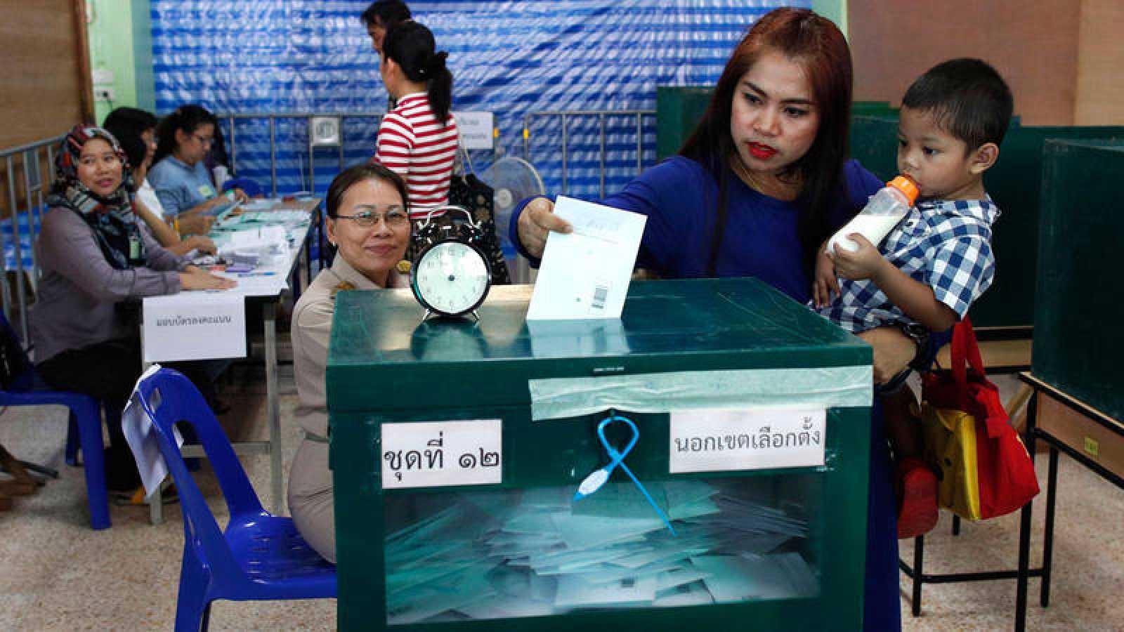 Una mujer con un niño en brazos deposita su voto en la urna durante las elecciones anticipadas de este lunes