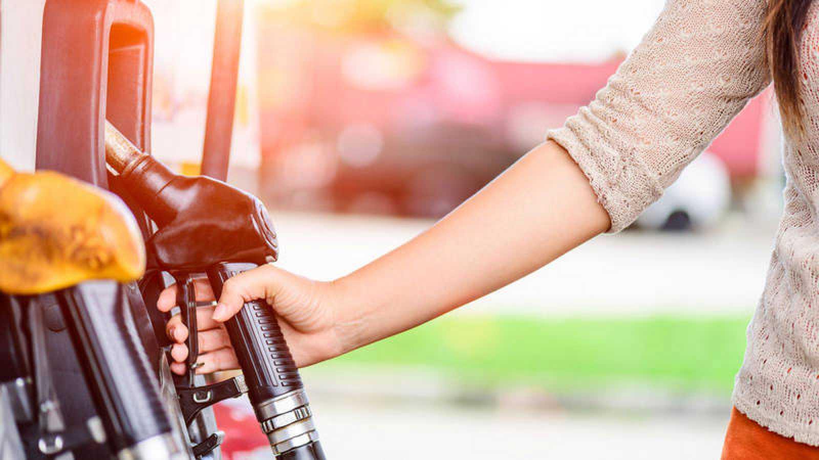 Una mujer reposta combustible en una gasolinera