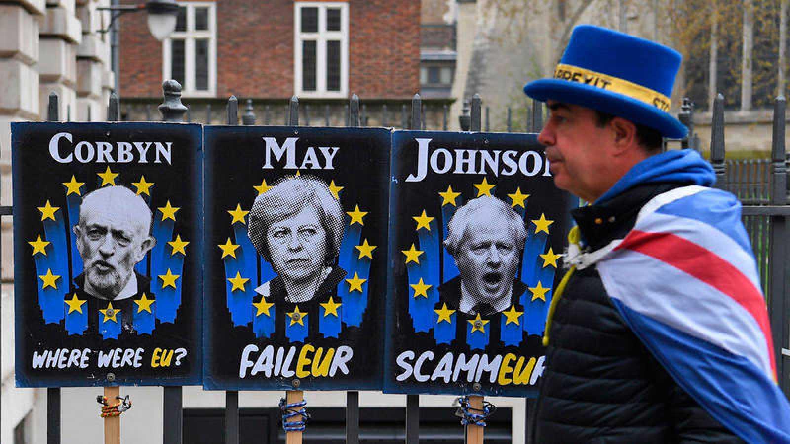 Un manifestante a favor de la estancia del Reino Unido en la Unión Europea camina junto a carteles que critican a Jeremy Corbyn, Theresa May y Boris Johnson en Londres.