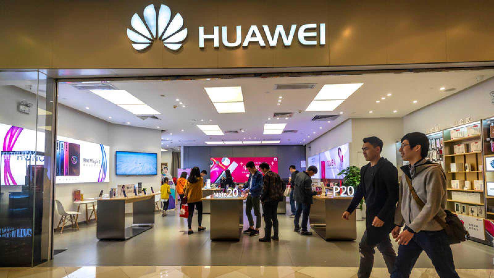 Dos hombres caminan frente a una tienda de Huawei.