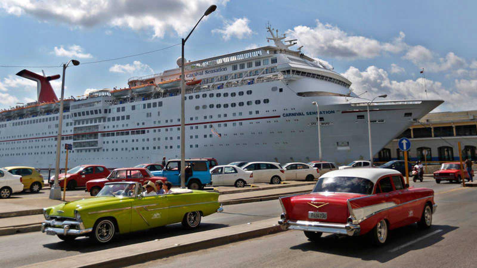 Dos coches estadounidenses clásicos pasan frente a un crucero anclado en el puerto de La Habana