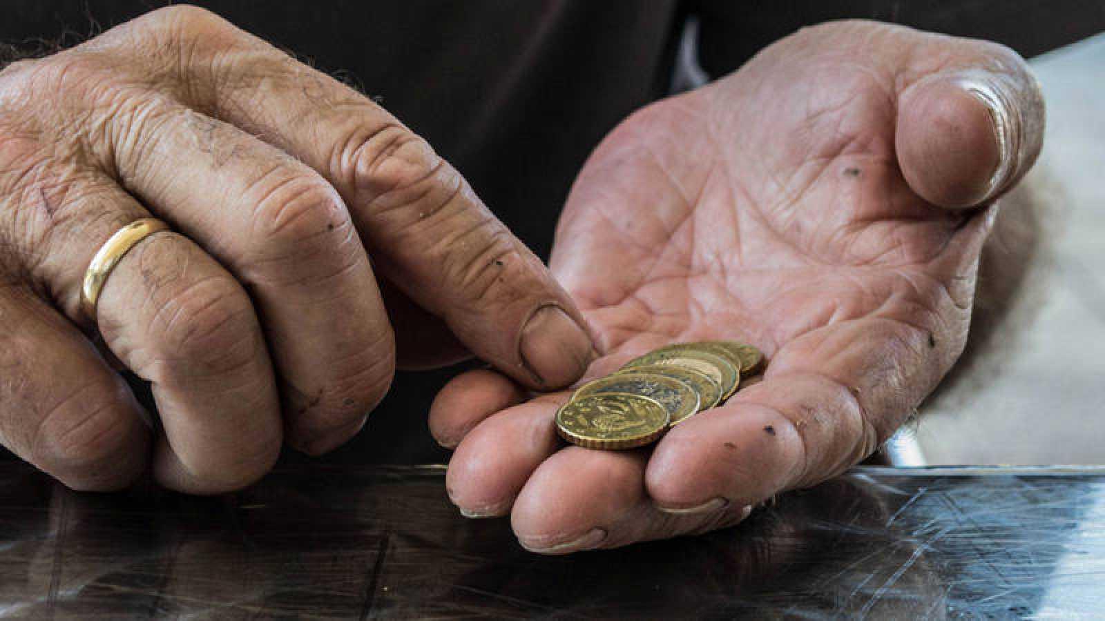 Un jubilado cuenta unas monedas