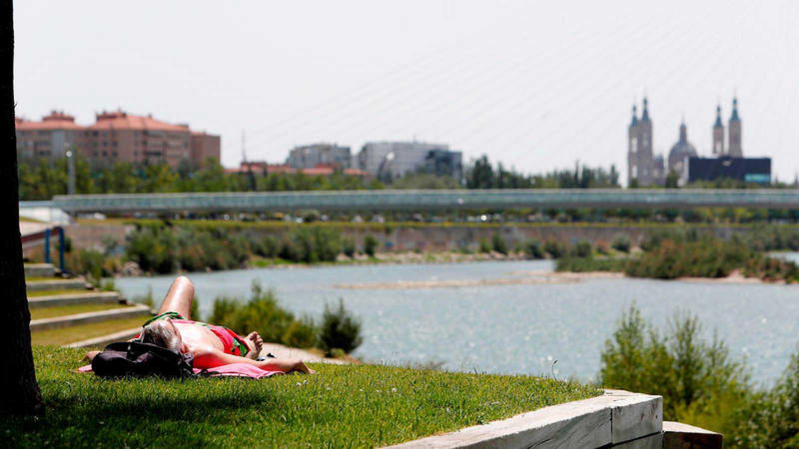 En la imagen, un hombre toma el sol en la ribera del Ebro.