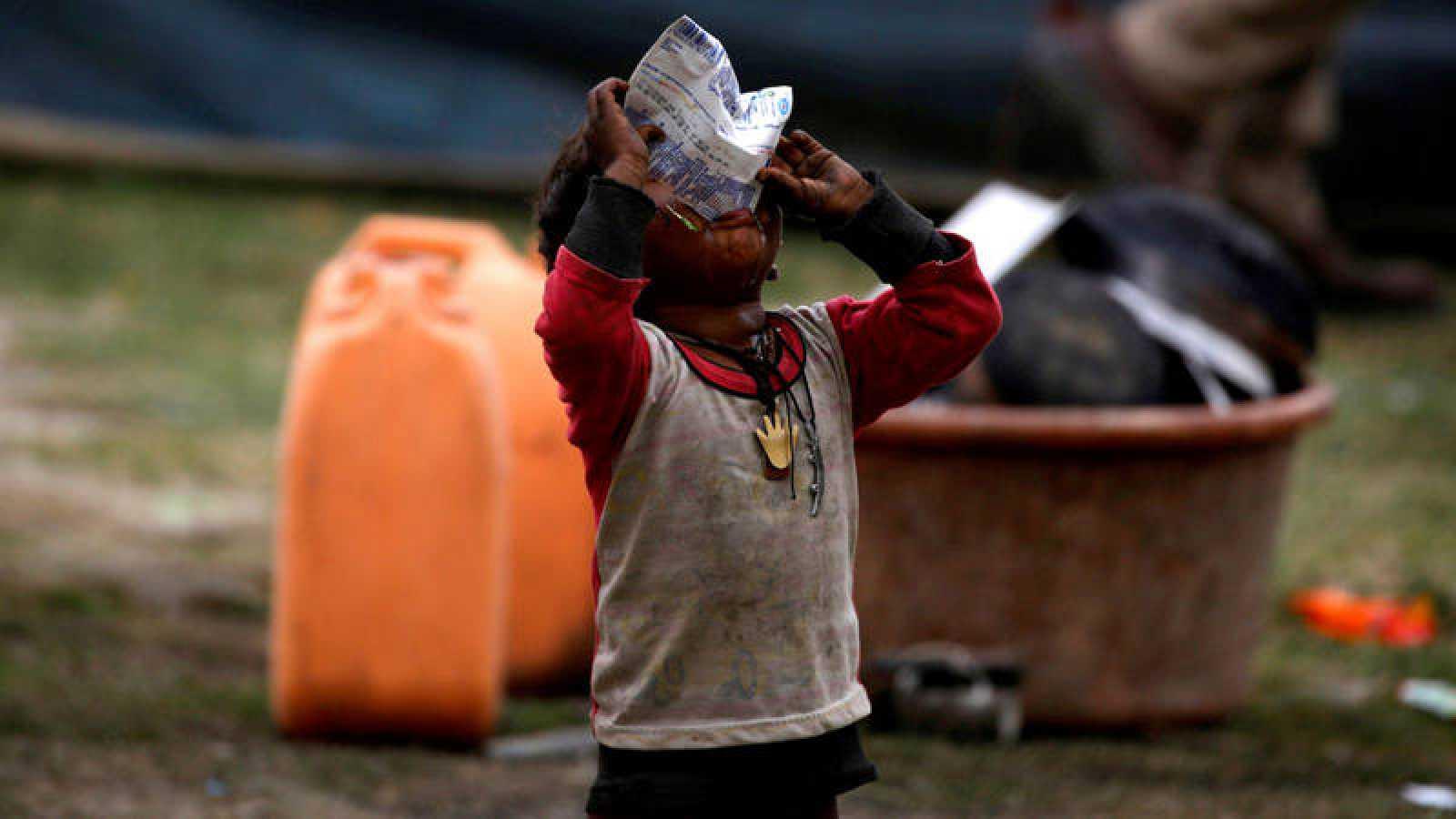 Un niño se alimenta en un campamento en Cachemira (India)