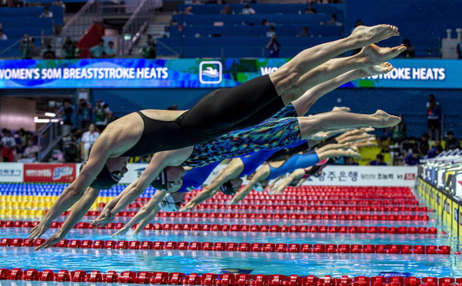 Las nadadoras de una serie de los 50 braza se lanzan a la piscina