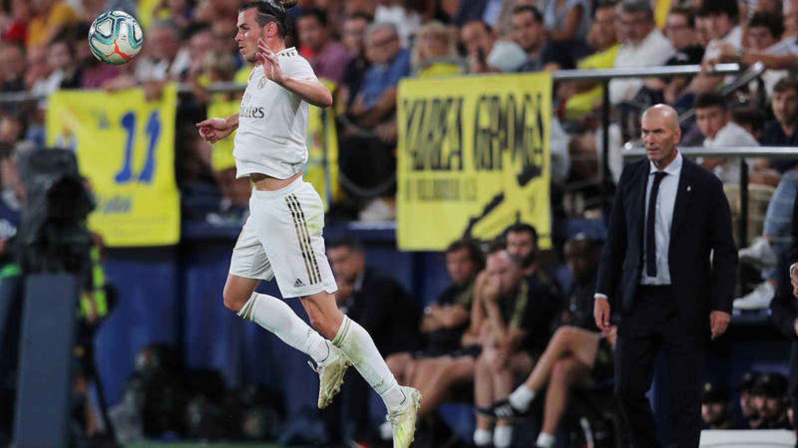 Bale controla un balón ante la mirada de Zidane