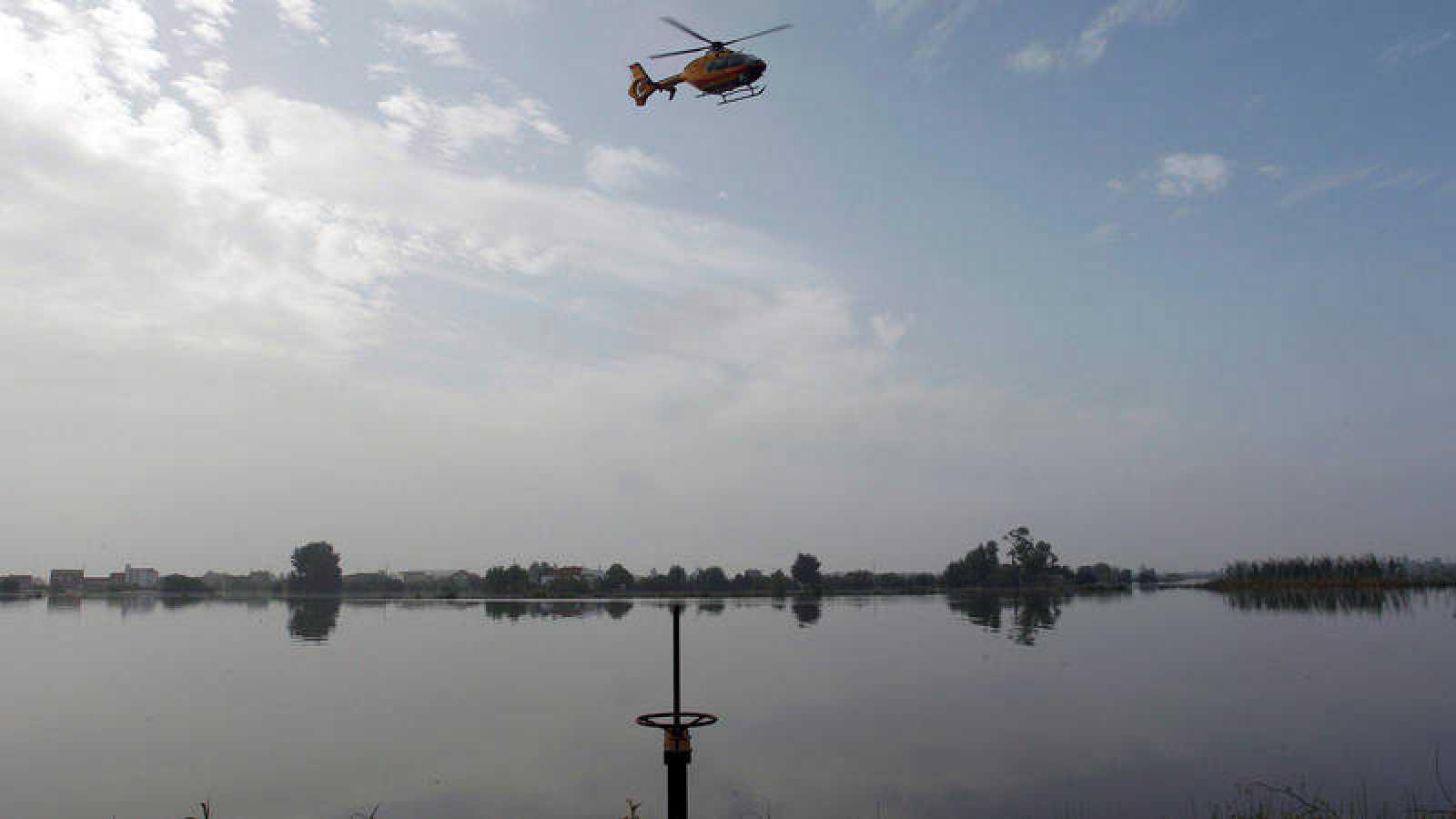 Gota fría: Un helicóptero busca en la zona donde el hombre desaparecido fue arrastrado por el agua en Dolores, Alicante.