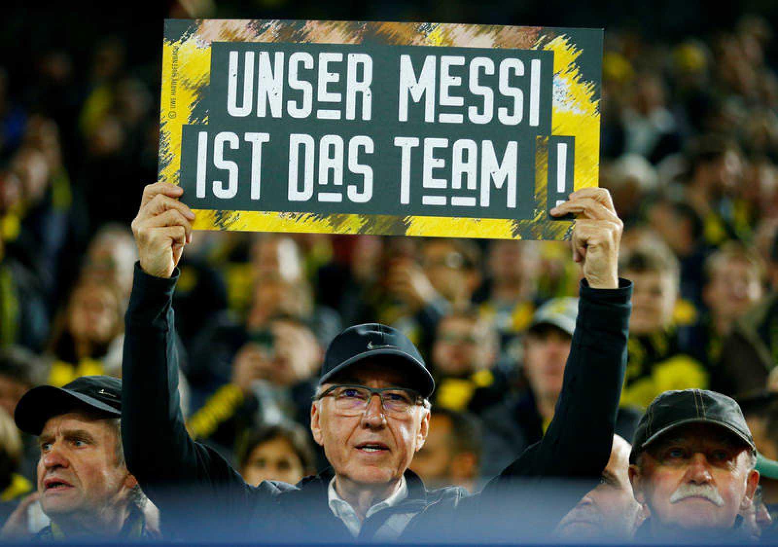 """Un aficionado del Dortmund muestra una pancarta que dice en alemán: """"Nuestro Messi es el equipo"""""""