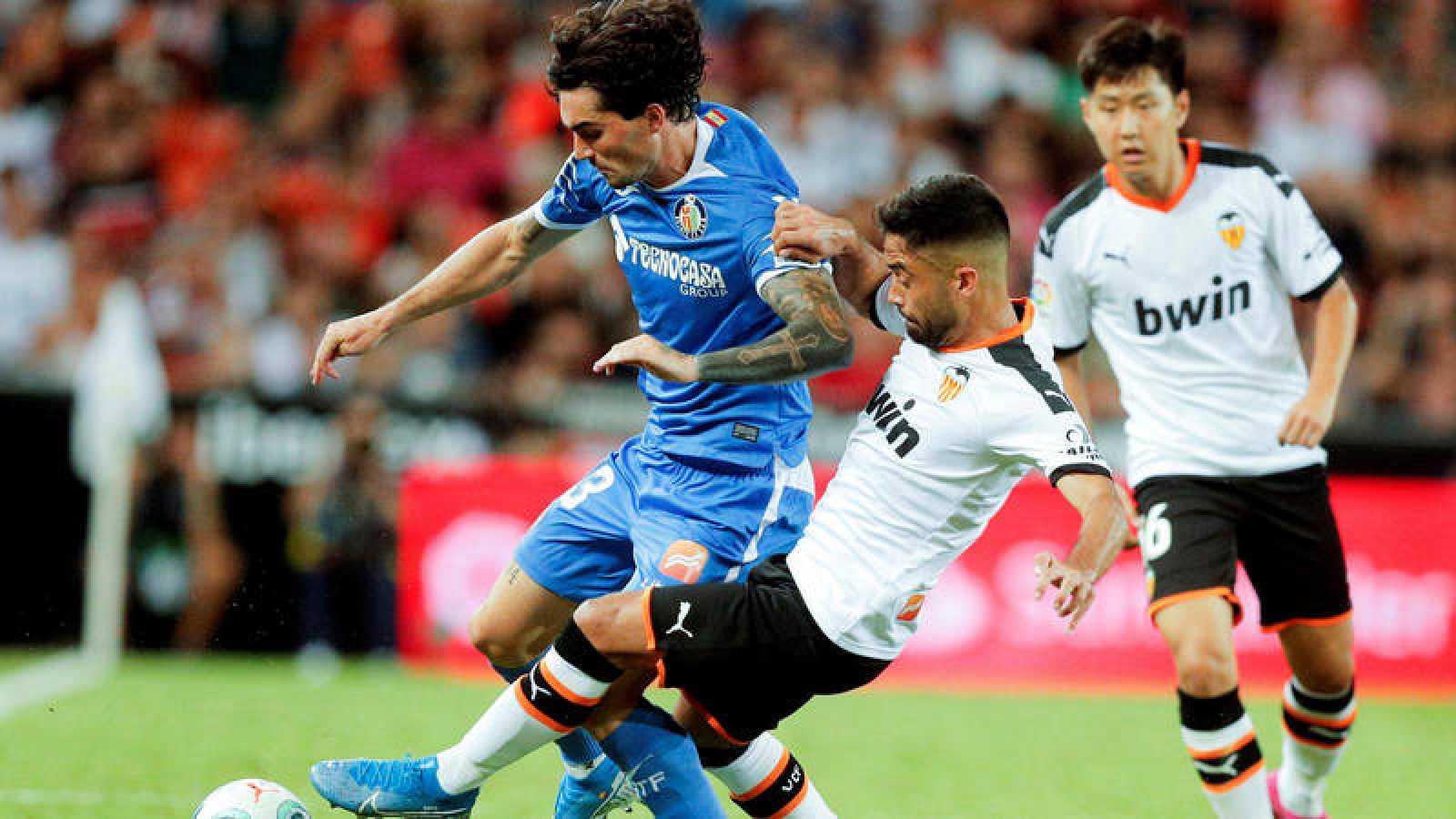 El valencianista Jaume Costa (d) disputa un balón con Jason (i), del Getafe CF
