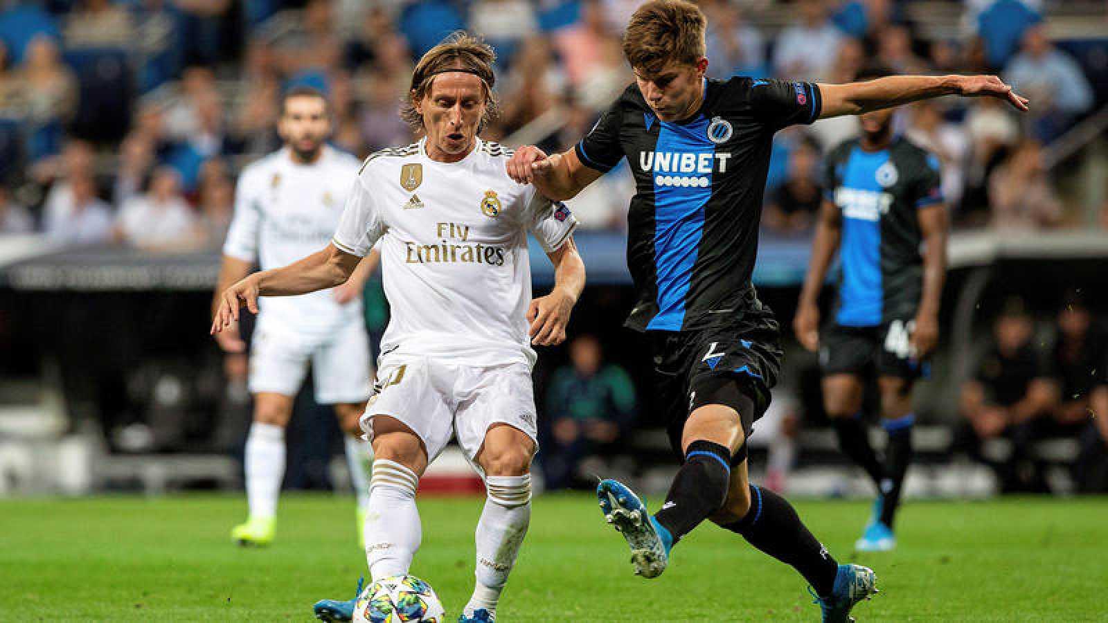El centrocampista croata del Real Madrid, Luka Modric pelea un balón con el defensa ucraniano del Club Brujas, Eduard Sobol.