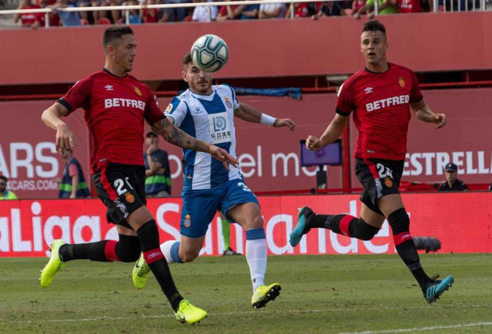 Víctor Campuzano (c) disputa el balón con Antonio José Raillo (i)