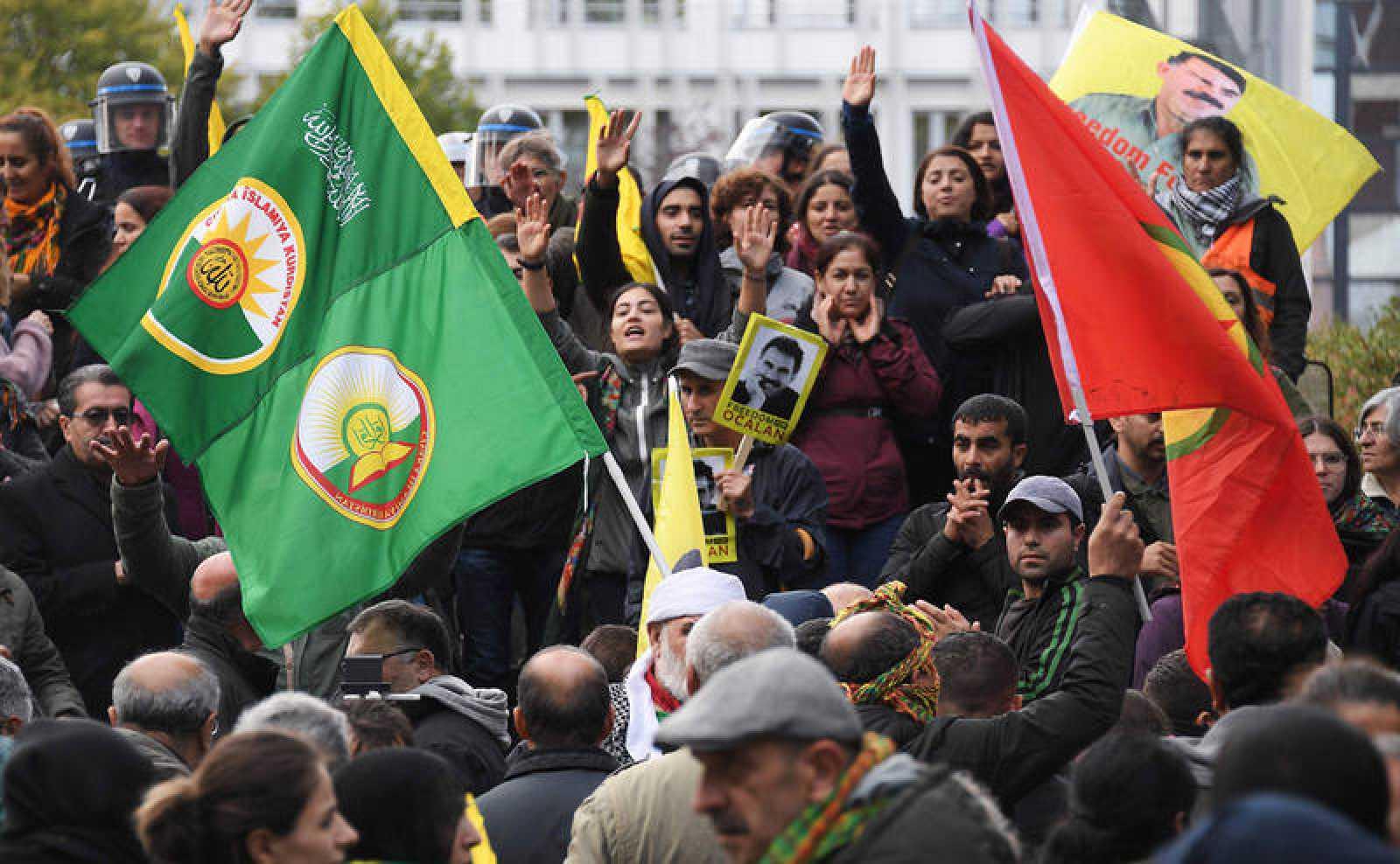 Los manifestantes kurdos agitan banderas y retratos del líder kurdo Abdullah Ocalan frente al Consejo de Europa en Estrasburgo, en el noreste de Francia, para protestar contra la acción militar de Turquía