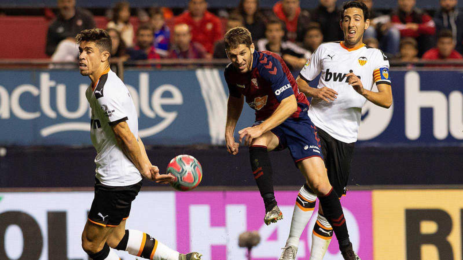 El centrocampista del Osasuna Darko Brasanac lanza ante la oposición del defensa Valencia Gabriel Paulista.