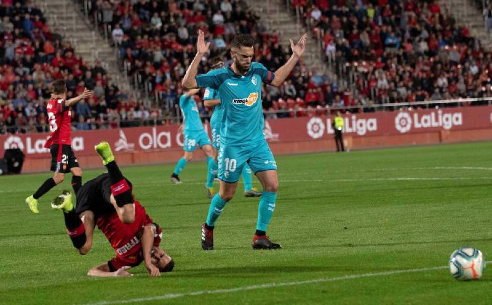 El jugador del Mallorca Dani Rodríguez (i) cae ante el del Osasuna Roberto Torres (d), este jueves durante el partido de la undécima jornada de Liga en el estadio Son Moix