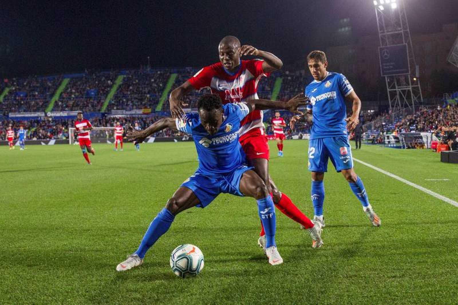 El defensa del Getafe Djené Dakonam (delante) protege el balón presionado por Darwin Machís, del Granada