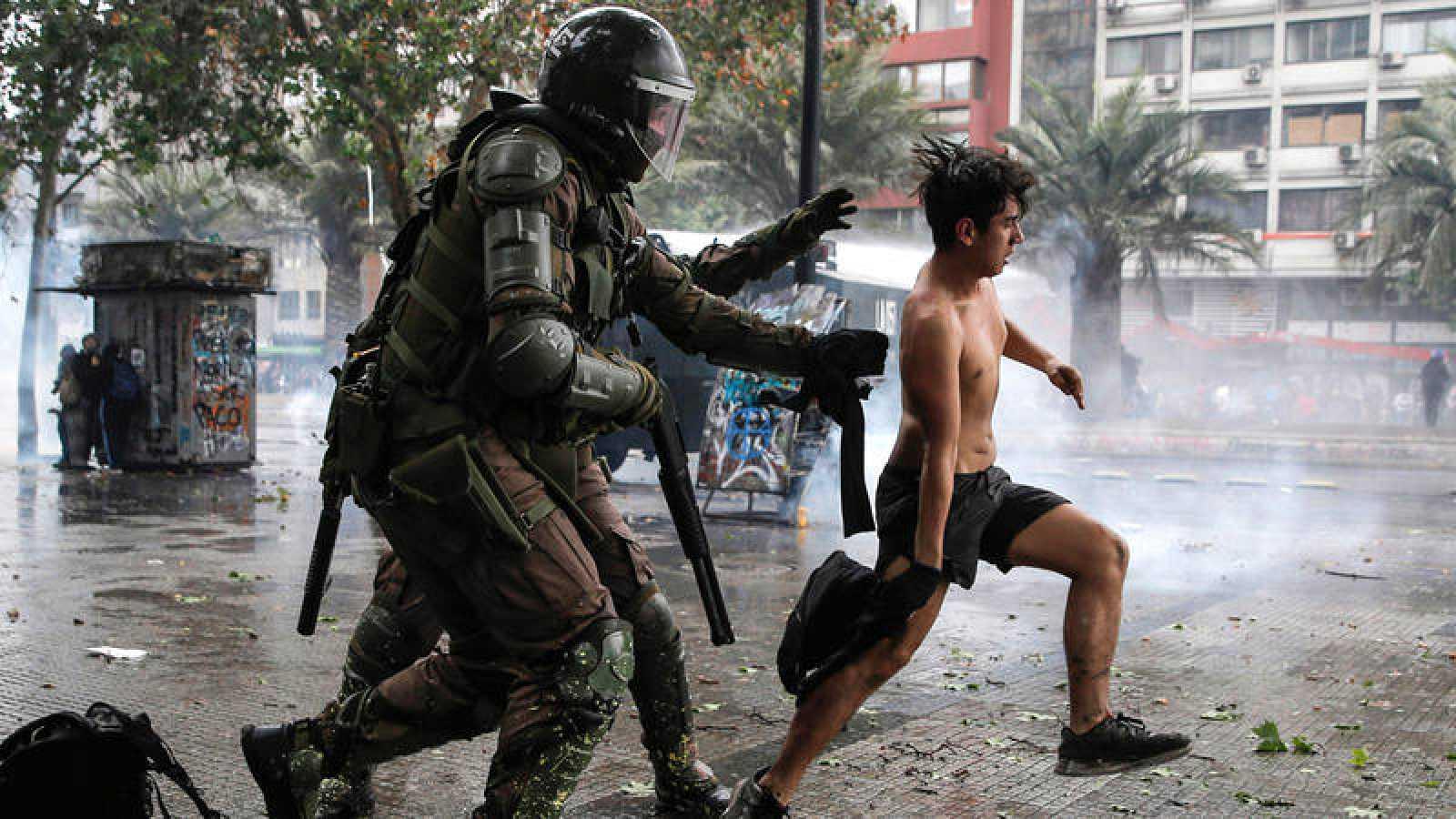 Policías antidisturbios persiguen a un manifestante en Santiago