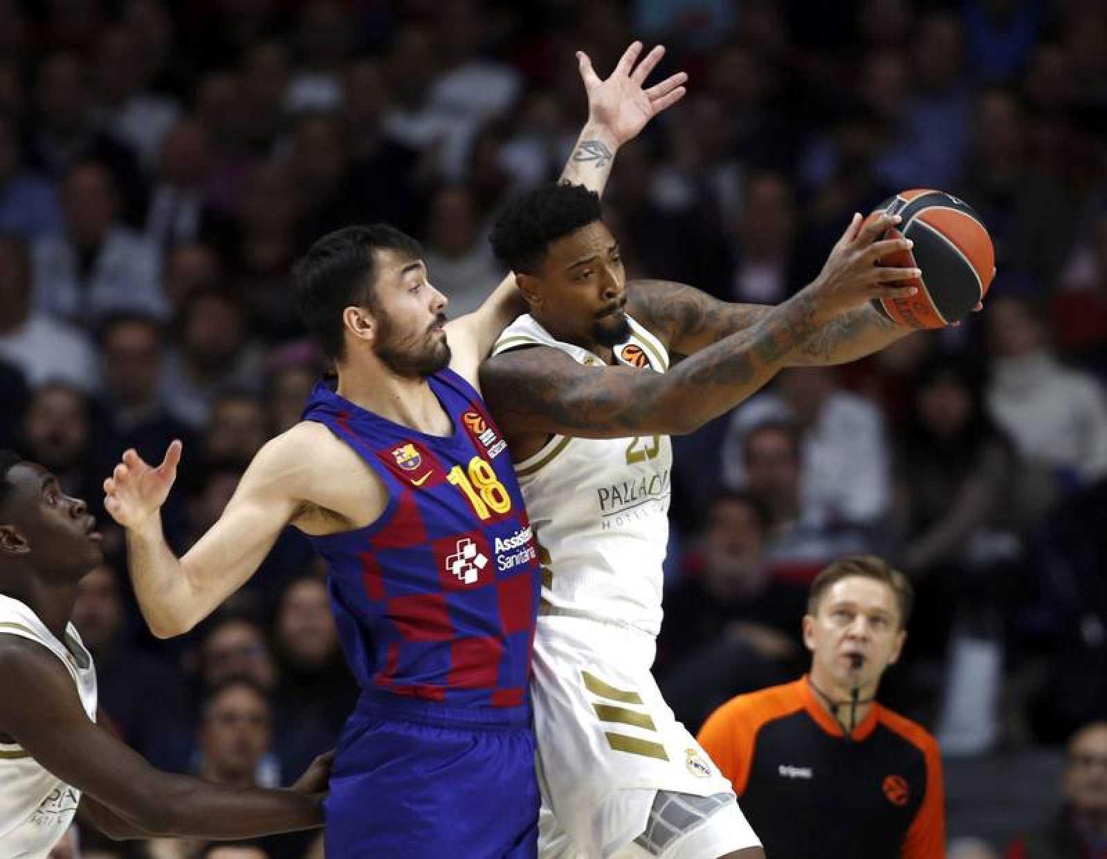 El pívot estadounidense del Real Madrid Jordan Mickey (d) lucha un balón con el ala-pívot del Barcelona Pierre Oriola (i)