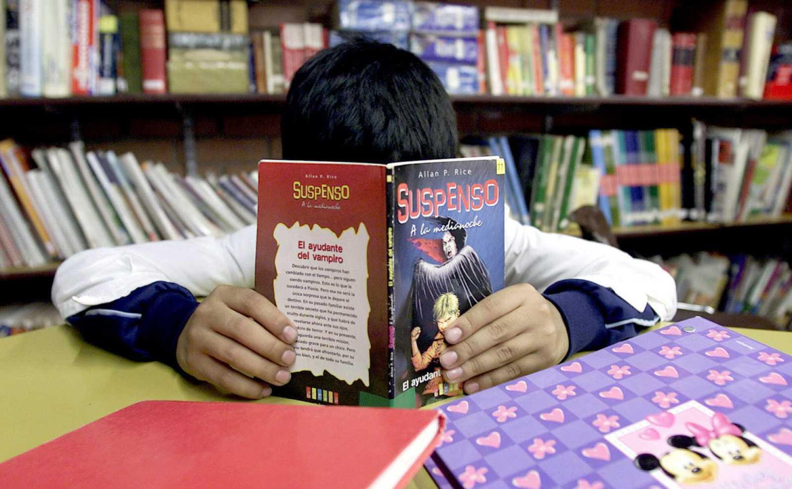 """Un niño lee en una biblioteca un libro titulado """"Suspenso"""""""