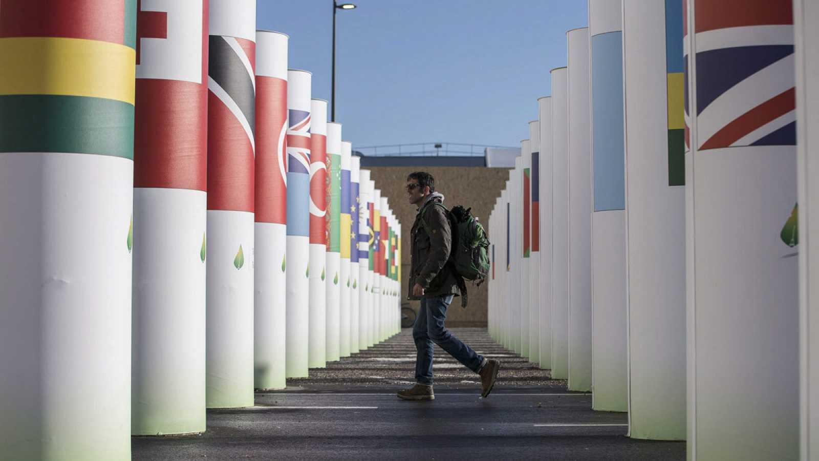 Un hombre camina entre unas columnas con las banderas de los países participantes en la COP21 de París