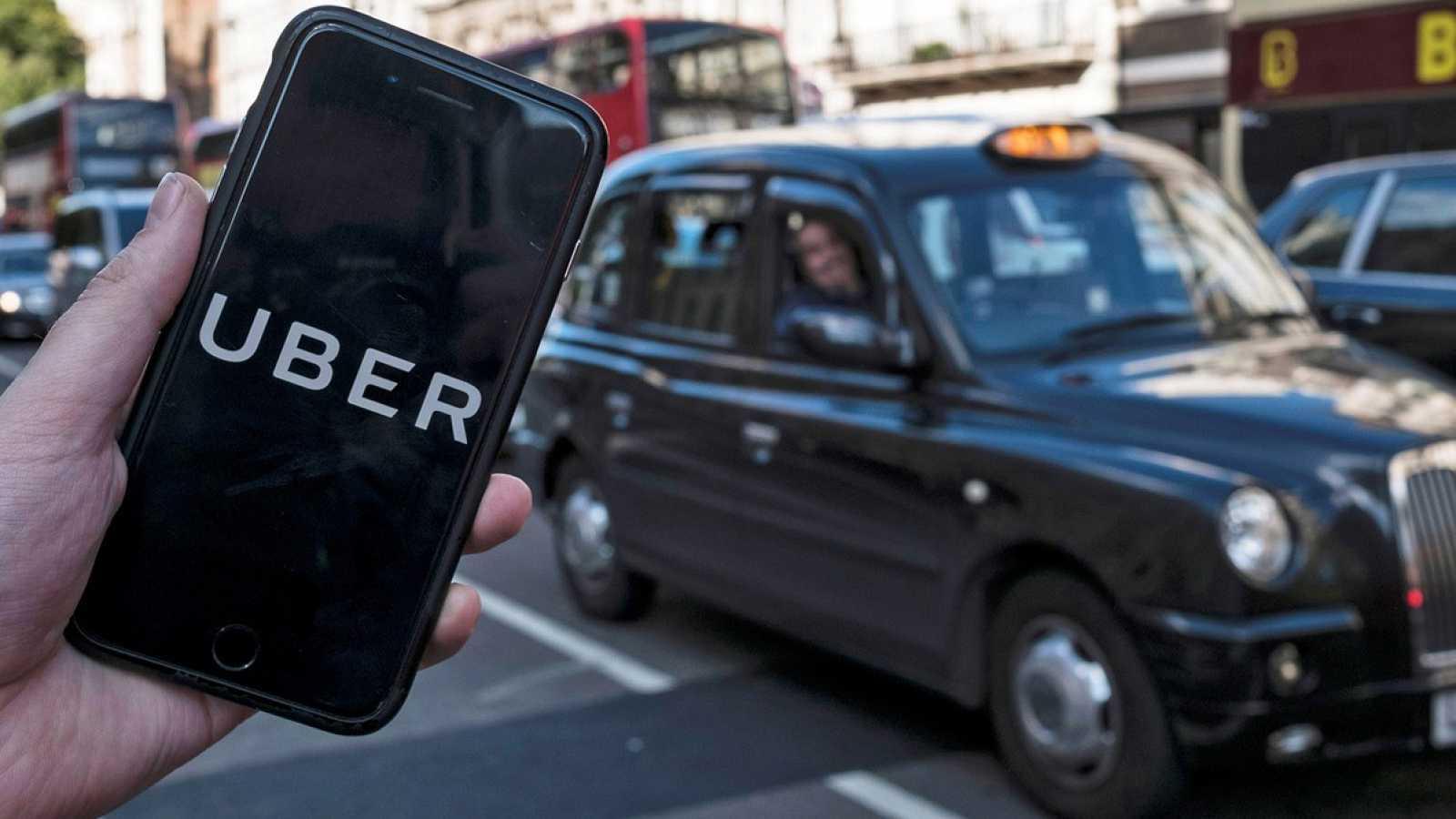 Un móvil con la aplicación de Uber frente a un taxi tradicional en Londres.EFE/EPA/WILL OLIVER