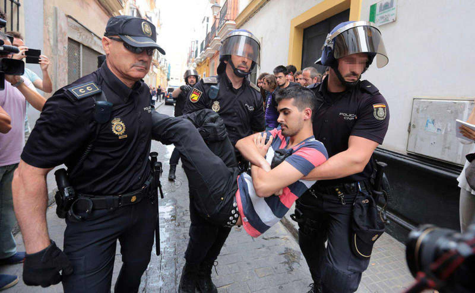 Agentes de la Policía Nacional llevan a una de las personas que intentaban evitar un desahucioa una familia que vivía en su casa de Cádiz en régimen de alquiler pero que finalmente fue desalojada en 2015 por una orden judicial.