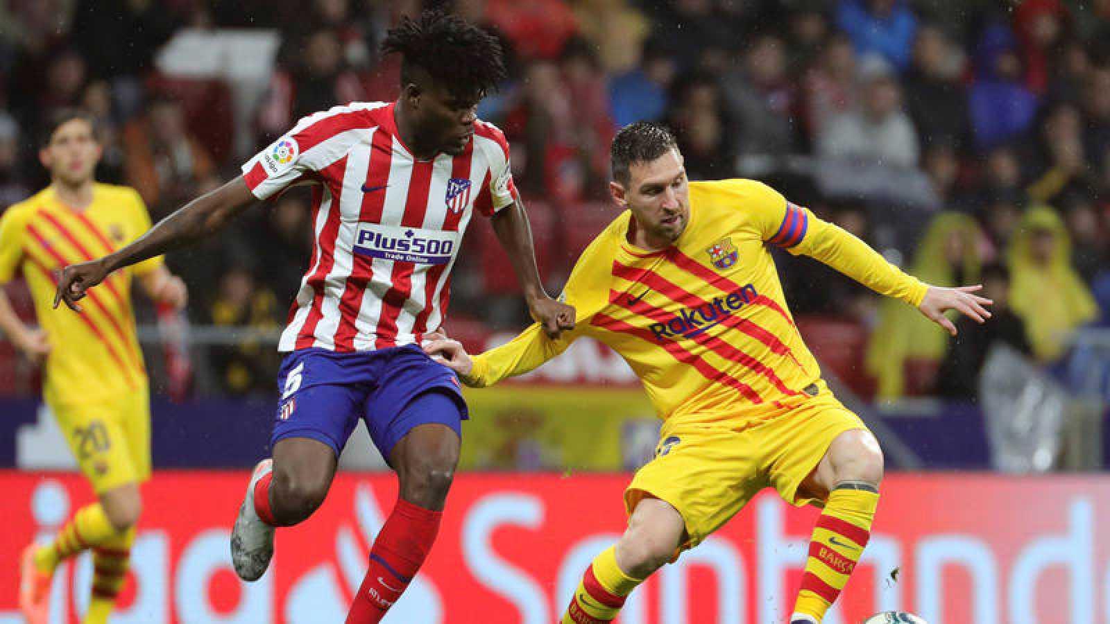El centrocampista ghanés del Atlético de Madrid Thomas Partey (i) persigue a Leo Messi (d), delantero argentino del FC Barcelona