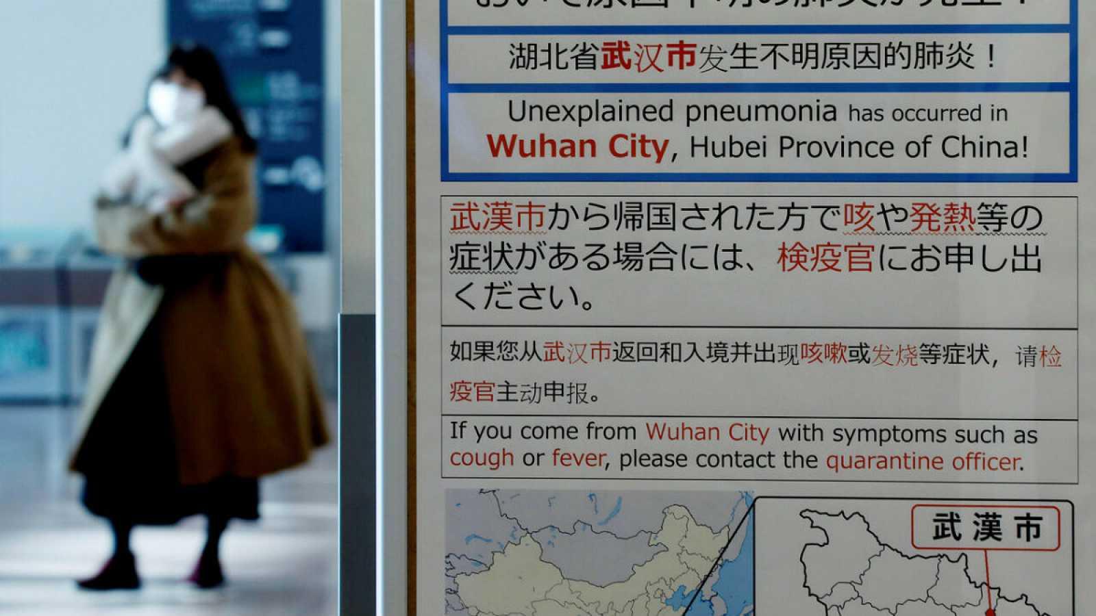 Una mujer camina con una máscara, dejando atrás un panel de información en el que se advierte del brote de coronavirus en China, en el aeropuerto Haneda, en Tokio.