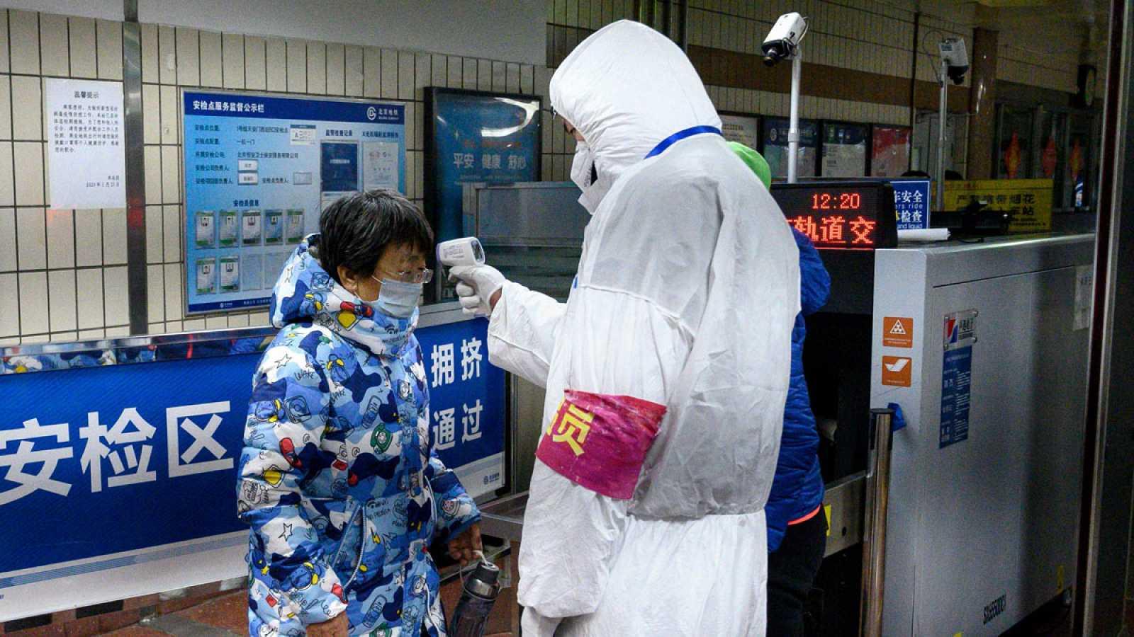 Comprueban la temperatura de los pasajeros en la entrada a una estación de metro en Pekín.