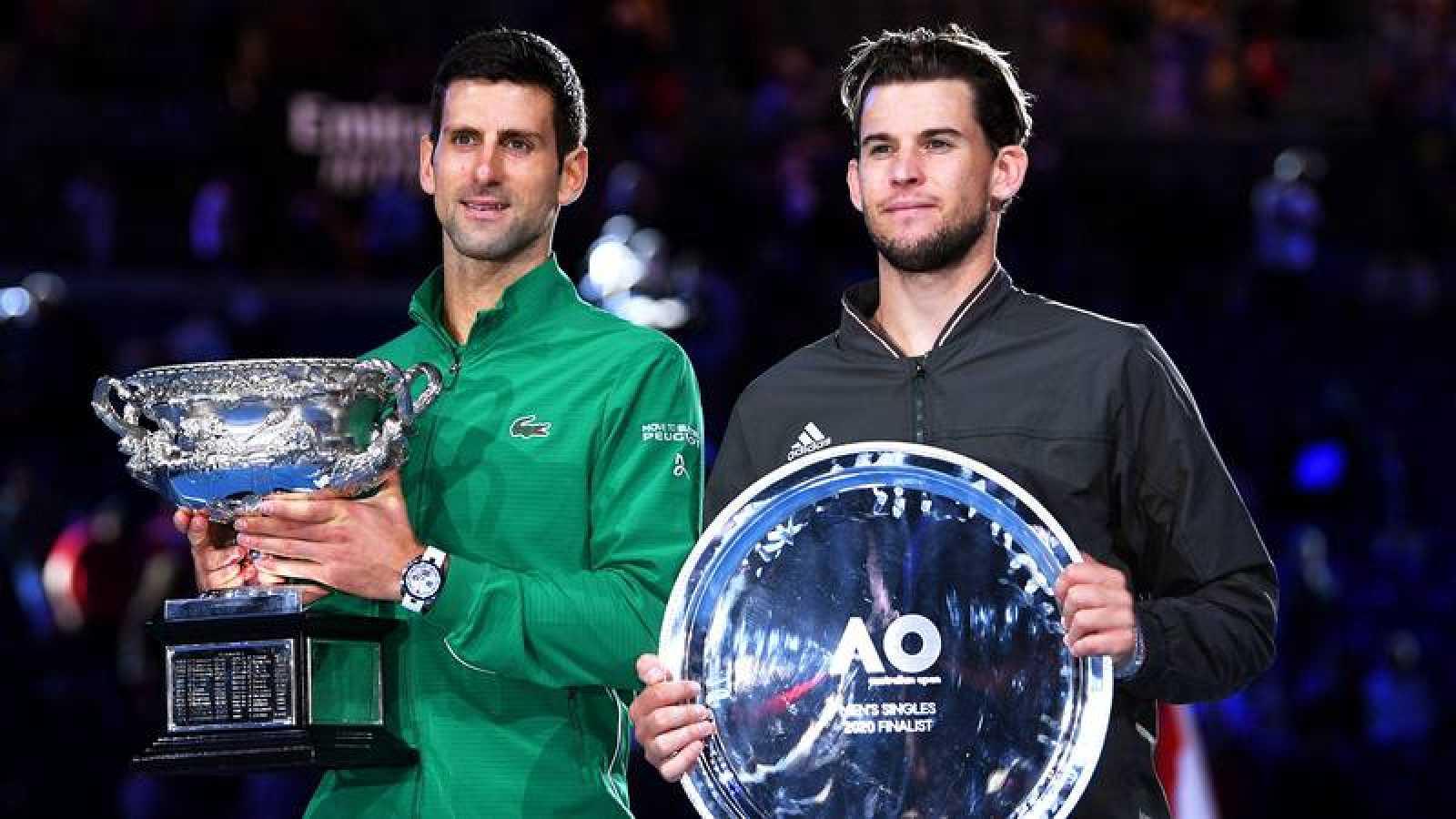 Novak Djokvic y Dominic Thiem posan con sus trofeos tras la final del Abierto de Australia 2020.